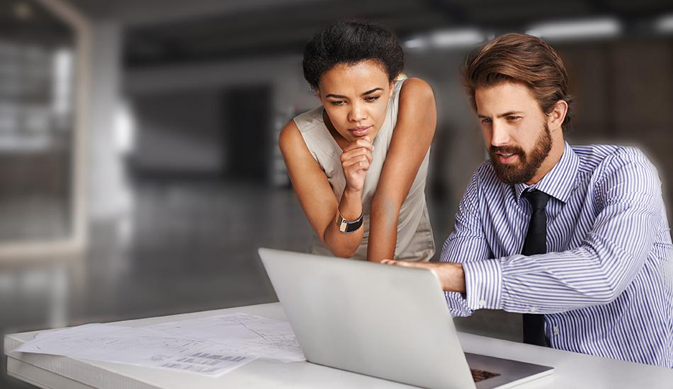 Man showing woman something on screen